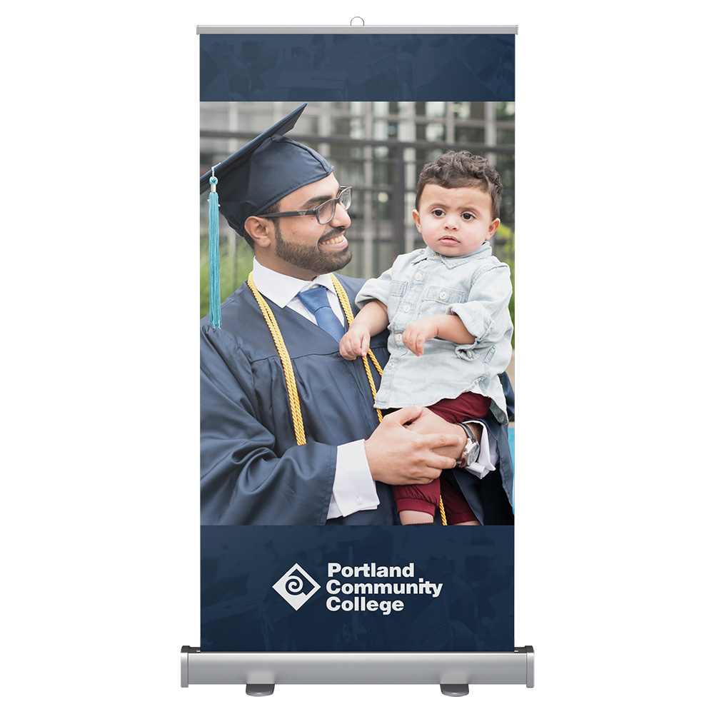 Wide banner stand with graduate student holding their son