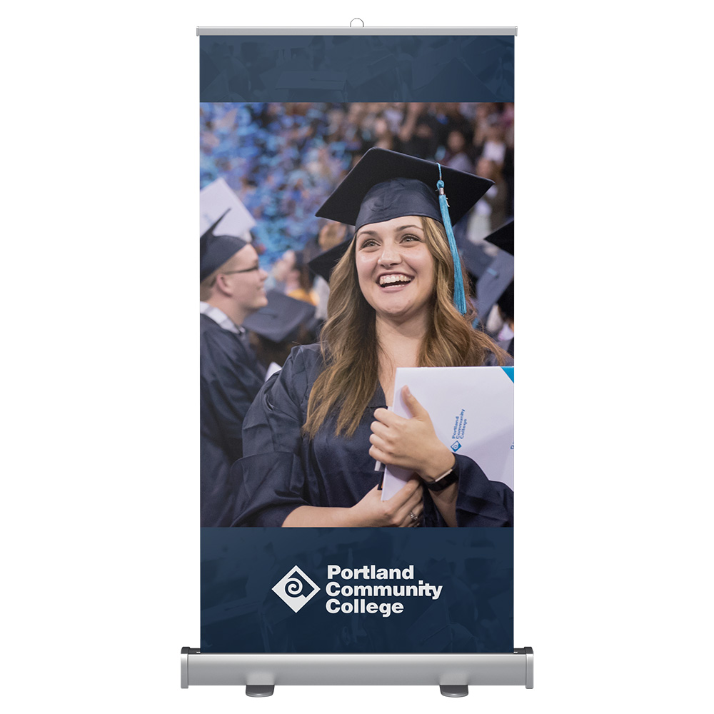 Wide banner stand with student celebrating at graduation