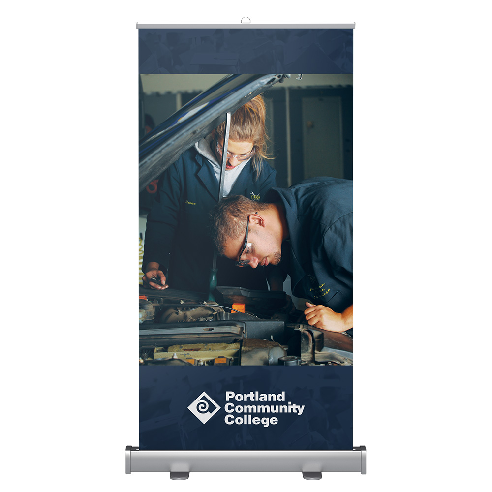 Wide banner stand with automotive students working on a car