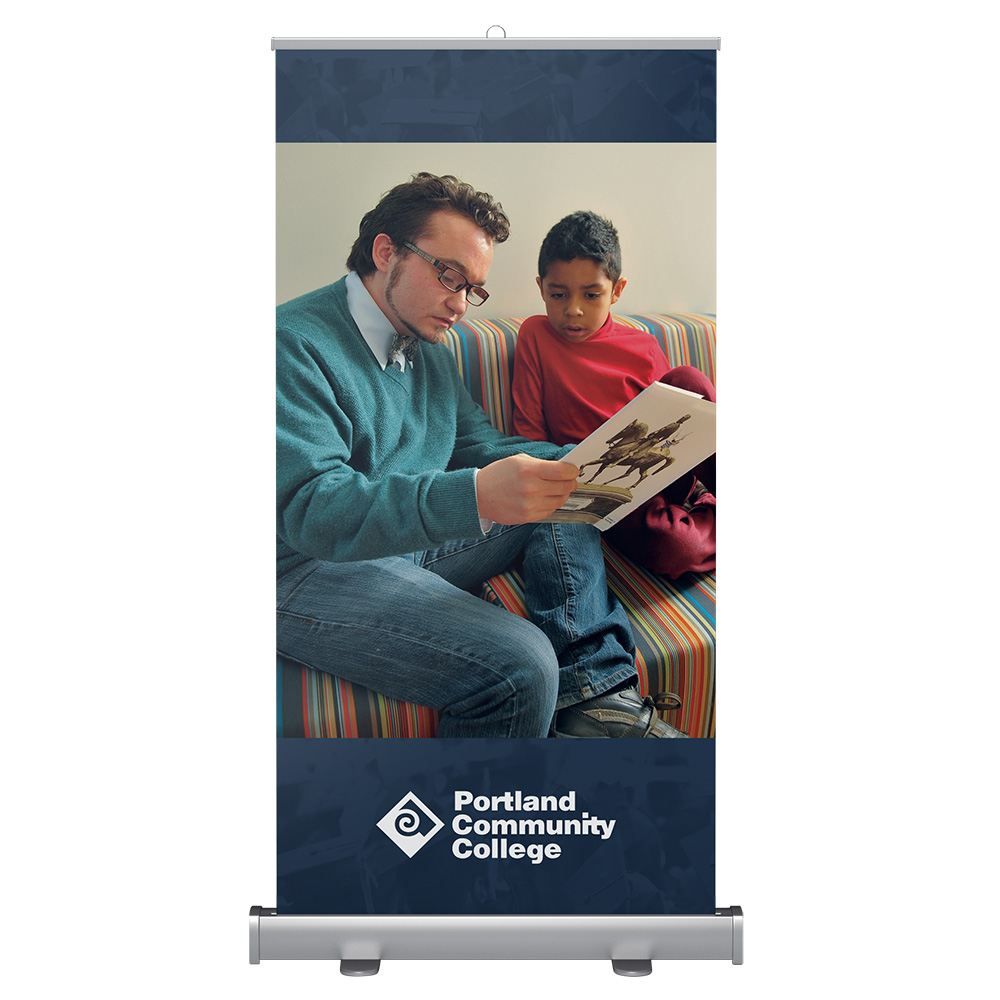 Wide banner stand with childhood education student reading to a child