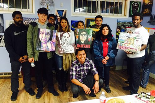 Multicultural Center students holding artwork created by youth from the community