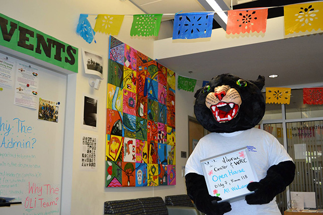 Poppy the Panther standing in front of a mural holding a sign that reads wrc and mc open house