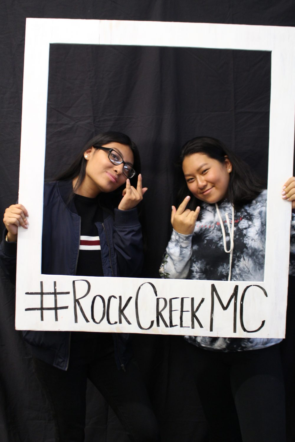 Two students holding up a fake Polaroid frame around their faces with the hashtag #RockCreekMC