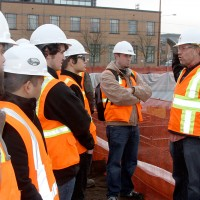 Derrick Beneville, project manager for Hoffman, discusses with the PCC students the kinds of jobs that are on the Cascade construction site. On the right, surveyor Darryl Ming of Ming Surveyors, Inc., scopes out the area.
