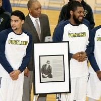 players standing with the commemorative plaque
