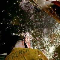 Student welding, with lots of sparks flying
