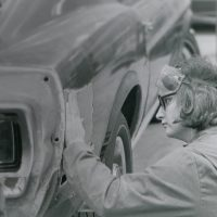 Black and white photo of a student working on a car in the 1970s
