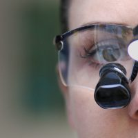 Woman wearing dentists' binoculars