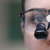 Woman wearing dentists' binoculars