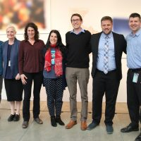 Faculty and staff pose in blurred out art gallery.