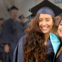 Two women smiling in their graduation caps and gowns