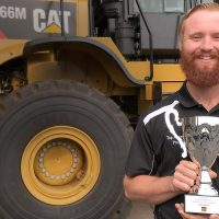 Ryan Walker holding his trophy in front of a CAT