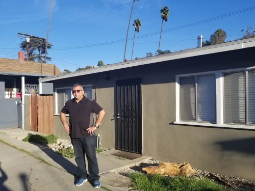 Villa standing outside his childhood home in East L.A. where he'd take a bus across town to attend Catholic school.