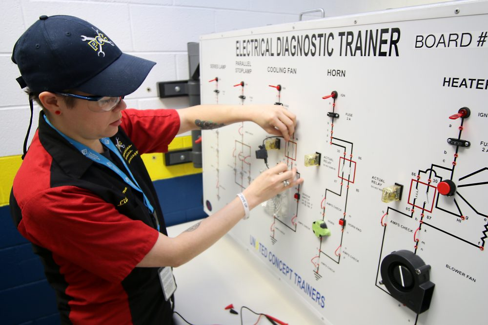 Boone works on an electrical diagnostic board used in auto training.