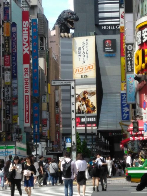 Photo of Godzilla over Toho theater and the busy crowd of Shinjuku.