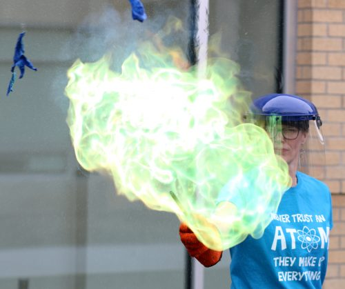 Chemistry instructor Karen Radakovich lights a balloon filled with a salt compound.