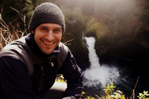 man wearing knit cap posing with waterfall in background