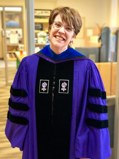 Dr. Jessica Howard poses in her regalia from NYU