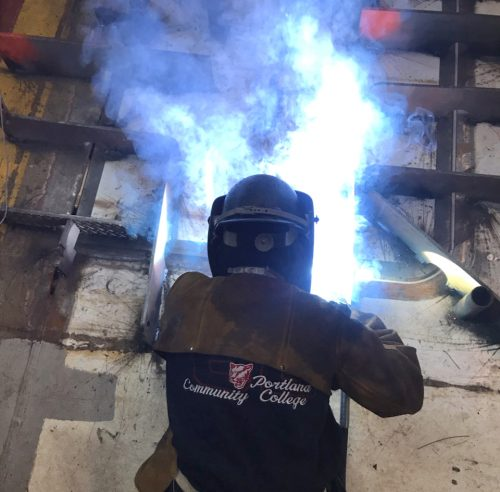 Jess welds with blue flame.