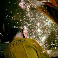 Maritime welder with sparks flying.