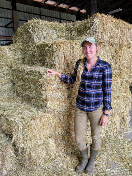 woman standing next to bales of hay
