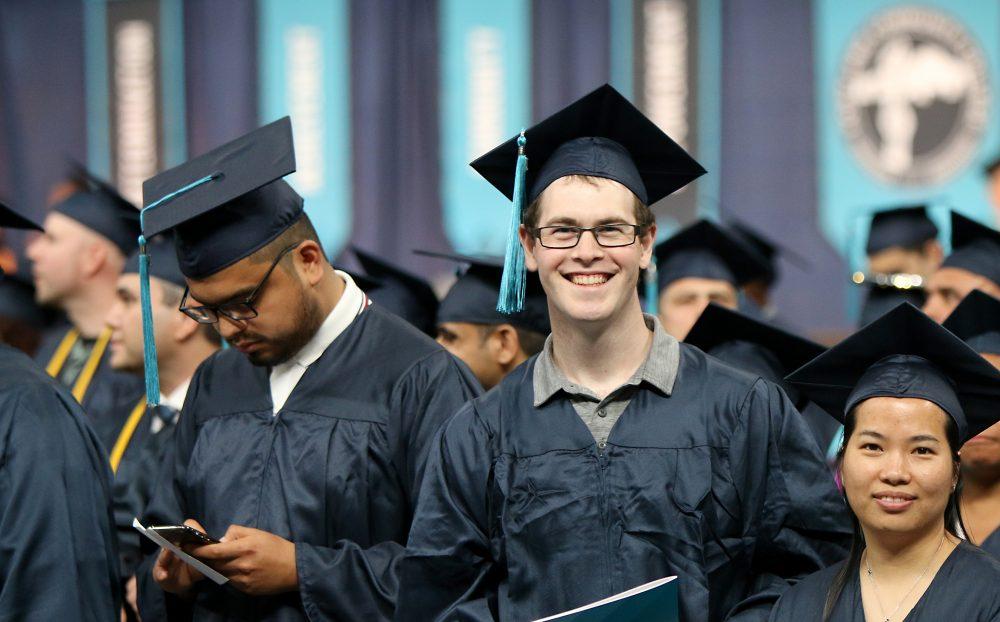 Student smiles on coliseum floor.