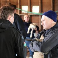man listening to a student in a barn