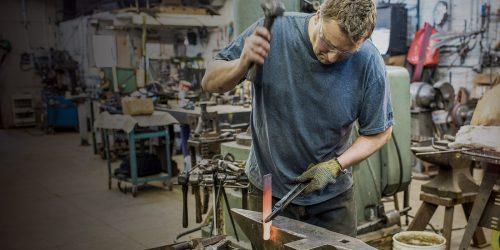Arnon Kartmazov working in his blacksmithing shop on a red-hot piece of metal
