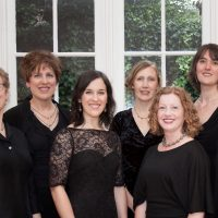 six women in black dresses