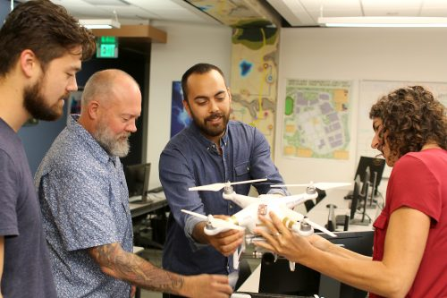 Christina Friedle helps students build a multi-rotater drone.
