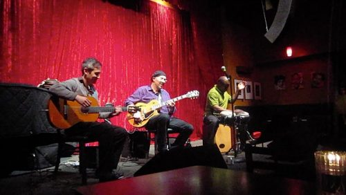 three men playing guitars and drum