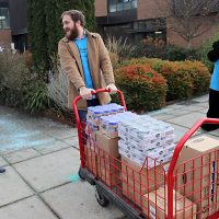 Students haul away food boxes to stock the pantry.