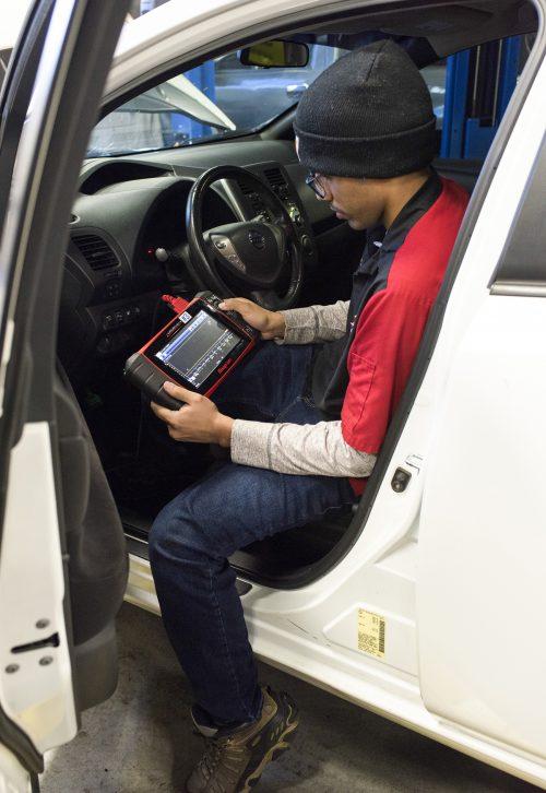 Luna performs a diagnostics test on one of PCC's shop vehicles.