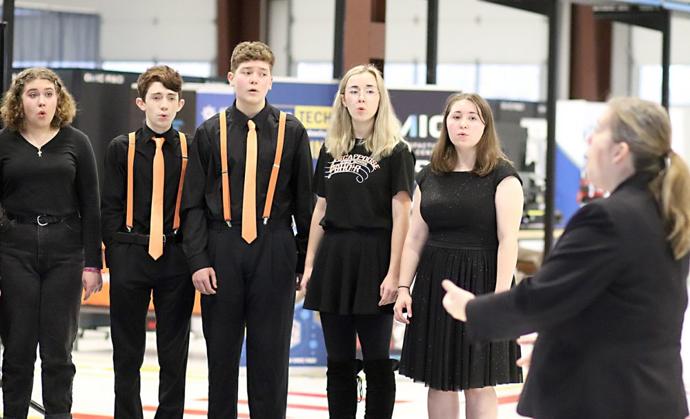 The Scappoose High School Choir sings for attendees.