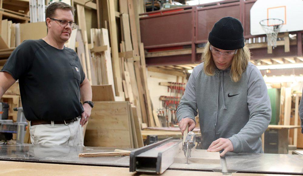 Alex Block carves a piece of wood.