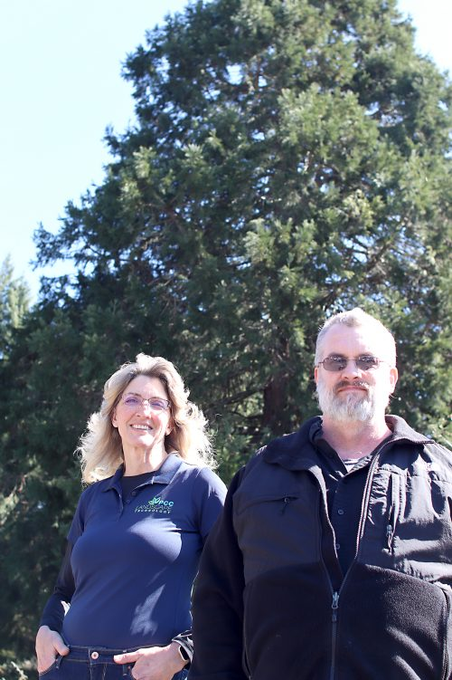 Anne LeSenne and Jack Lussier pose in front of trees.
