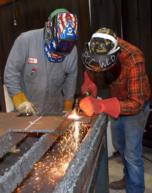 Instructor Scott shows Kevin Hagard welding technique.
