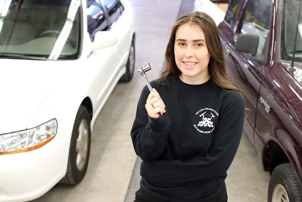 Taylor Berglund poses with a wrench in her hand at the auto shop.