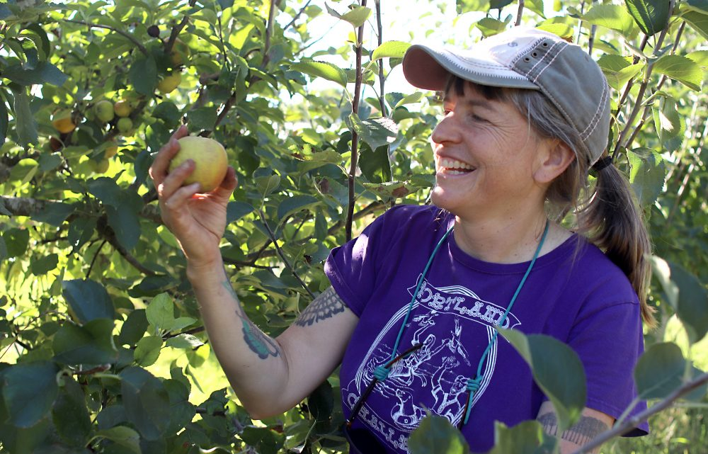 Miriam Latzer with apple in the orchard.