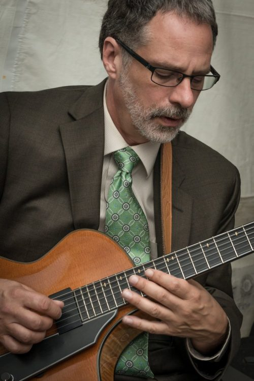 Man in suit holding guitar