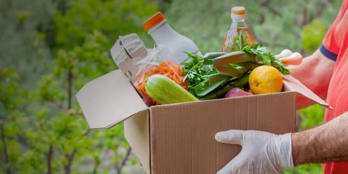 Delivery during the quarantine o food donation concept. A man holding cardboard box in medical gloves with vegetables, fruits and other food. Assistance at quarantine time because of coronavirus infection Covid-19.