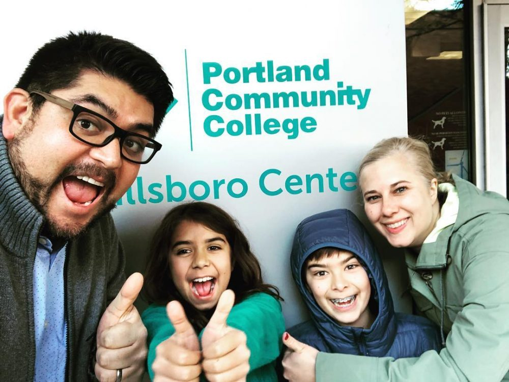 Family posed giving thumbs up and smiling in front of PCC Hillsboro Center sign