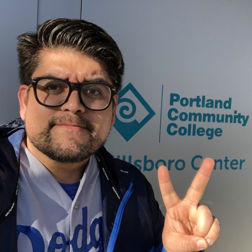 Esparza flashing peace sign in front of PCC Hillsboro Center sign