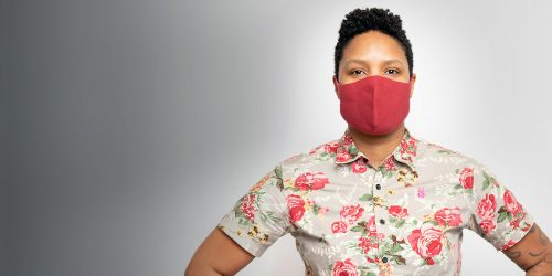 Ebony Frison standing with hands on hips and wearing a mask