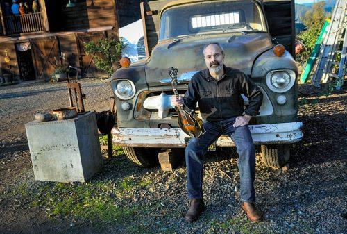 man holding mandolin sitting on an old truck
