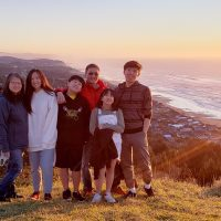 Family of six poses on a bluff overlooking the ocean