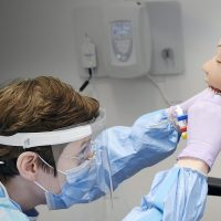 Dental student working on a model robot patient