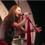 Metal vocalist Gene Summers sings into a microhone.
