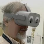 Instructor Seth Bloombaum wearing an Oculus Go which has large google eyes applied to the face of it where human eyes would naturally be.