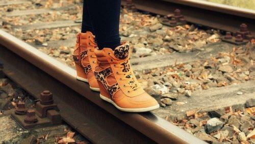Feet balancing on a railroad track